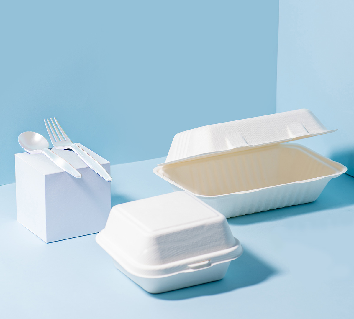 Compostable sugarcane containers and cornstarch cutlery over blue background
